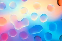 Vattendroppar med färgrik bakgrund Arkivbild