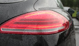 Vattendroppar på bakre ljus för bil efter anti-beläggning för regnskydd lagerför foto arkivbild
