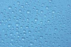 Vattendroppar på blå bakgrundstextur Arkivbild