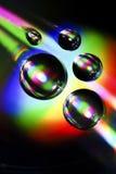 Vattendroppar på CD med den färgrika regnbågen arkivfoto