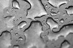 Vattendroppar på den skrapade stålplattan Arkivbild