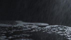 Vattendroppar på en svart yttersida som det regnar yttersidan, rotera lager videofilmer