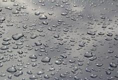 Vattendroppar på metallisk silver Royaltyfri Bild