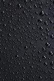 Vattendroppar på en svart plast- yttersida Royaltyfri Bild