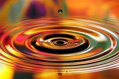Vattendroppar plaskar Röda och gula krusningar, reflexioner på yttersida arkivfoton