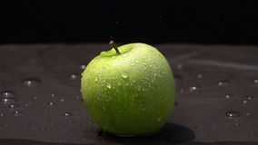 Vattendroppe på ett grönt äpple på svart bakgrund stock video
