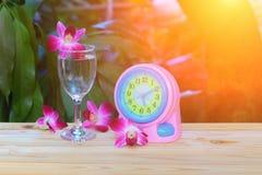 Vattenexponeringsglas med orkidélilor och klockan i trägolvet, suddighetsbakgrund brunnsortbegrepp med solnedgångljussignal Royaltyfria Bilder