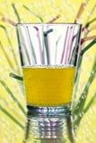 Vattenexponeringsglas med sugrör i bakgrunden Royaltyfri Fotografi