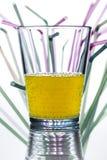 Vattenexponeringsglas med sugrör i bakgrunden Royaltyfri Bild