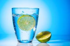 Vattenexponeringsglas och limefrukt Royaltyfria Bilder