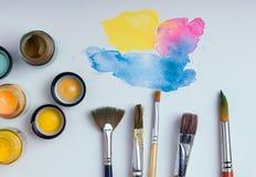 Vattenfärg och borstar på vit bakgrund Arkivfoto