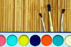 Vattenfärg- och målarfärgborstar ligger på tabellen royaltyfri fotografi