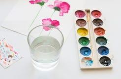 Vattenfärger, borsten och målning av härliga rosa färger blommar på vit bakgrund, konstnärlig arbetsplats Fotografering för Bildbyråer