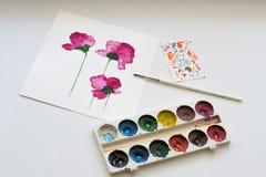 Vattenfärger, borsten och målning av härliga rosa färger blommar på vit bakgrund, konstnärlig arbetsplats Royaltyfria Foton