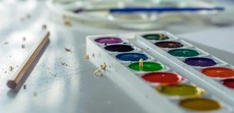 Vattenfärger, en borste och en blyertspenna royaltyfri fotografi