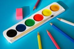 Vattenfärger, färgade blyertspennor och radergummilögn på en blå bakgrund arkivfoto