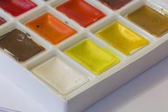 Vattenfärger i asken på en vit bakgrund Royaltyfria Bilder