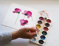 Vattenfärger måla av härliga rosa blommor, hand som rymmer en borste, på vit bakgrund, konstnärlig arbetsplats Arkivbild