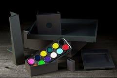 Vattenfärger och olika onstructions för svart Ñ på en trätabell Arkivfoton