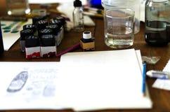 Vattenfärger på vitbok och vattenfärger på tabellen Arkivbild