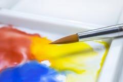 Vattenfärgmålarfärgborste på en vit palett Fotografering för Bildbyråer