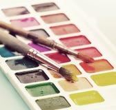 Vattenfärgmålarfärger och borste på tabellen Retro hipster för tappning Arkivbilder