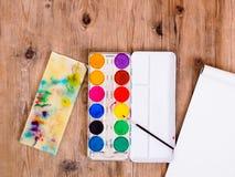 Vattenfärgmålarfärger och drablock på en brun trätabell, bästa sikt arkivbilder