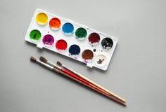 Vattenfärgmålarfärger och målarpenslar på grå bakgrund arkivfoton