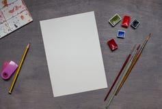 Vattenfärgmålarpenslar med färger och den plast- paletten Fotografering för Bildbyråer