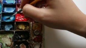 Vattenfärgmålning på det vita kanfasbakgrundsslutet upp lager videofilmer