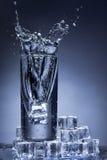 Vattenfärgstänk i ett exponeringsglas. Arkivbilder
