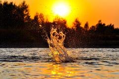 Vattenfärgstänk i floden under solnedgång Arkivbild