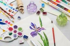 Vattenfärgteckning - irisblomma - och konstnärlig utrustning på skrivbordet royaltyfria foton