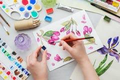 Vattenfärgteckning - rosa körsbärsröda blommor - och konstnärlig utrustning på skrivbordet Målareteckning på arbetsplatsen arkivbilder