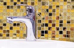 Vattenförsörjningvattenkranblandare på bakgrunden av gula keramiska mosaiktegelplattor arkivfoto