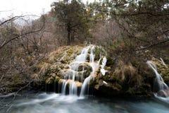 Vattenfall från en klippa i skogen arkivfoton