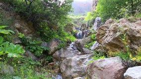 Vattenfall i bergen nära byn arkivfilmer