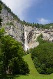 Vattenfall i de schweiziska fjällängarna Arkivfoto
