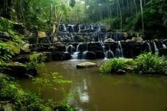 Vattenfall i djup skog Arkivbilder