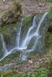 Vattenfall i mossan och stenarna för skoggräsplan Sommar Arkivfoton