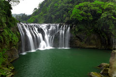 Vattenfall i skog Arkivbild