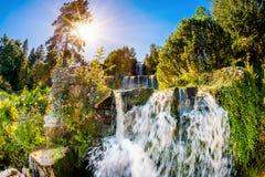Vattenfall i skogen med den ljusa solen i bakgrunden fotografering för bildbyråer