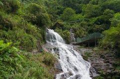 Vattenfall i skogen med turist- infrastruktur Arkivfoton