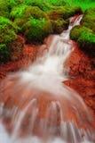 Vattenfall och röd jord röd vattenfall Vatten och ström n Arkivfoton