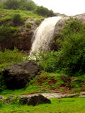 Vattenfall på grön back Arkivfoto