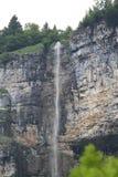 Vattenfall som droppar uppifrån av berget Arkivfoto