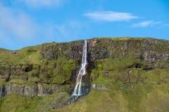 Vattenfall som spolar ner en grön bergssida royaltyfri foto