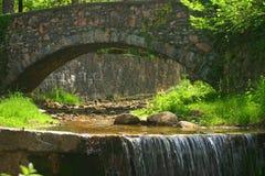 Vattenfall under en stenbro Royaltyfri Bild