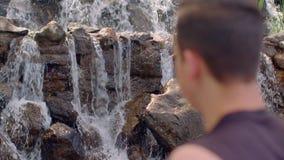 Vattenfallavkoppling Man som kopplar av på morgonen wrist för watch för avkoppling för begreppshandfack stock video