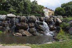 Vattenfallet i parkerar med gröna träd och gräs och det lilla dammet royaltyfri bild